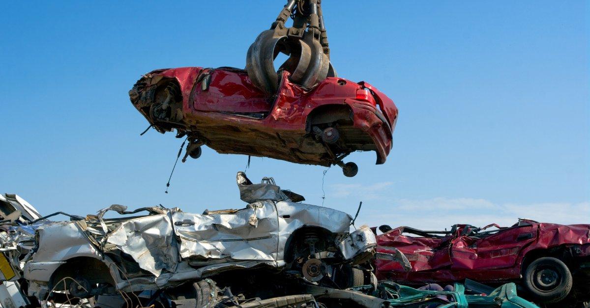 A scrap car being held by a claw in a scrap yard